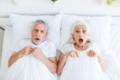 Hoge grijze het haarmensen van het hoek hoogste mening verraste paar in pyjama, royalty-vrije stock foto's