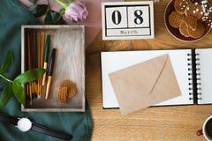 Hoge hoekfoto van houten die lijst met envelop op notitieboekje, vakje met borstels en pennen en koekjes in kom wordt geplaatst stock afbeelding