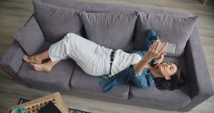 Hoge hoekmening die van leuk meisje selfie met smartphone nemen die op bank thuis liggen stock footage