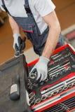 Hoge hoekmening die van mannelijke werktuigkundige hulpmiddelen in lade schikken bij autoreparatiewerkplaats royalty-vrije stock foto