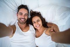 Hoge hoekmening die van paar zelfportret op bed nemen Royalty-vrije Stock Foto's