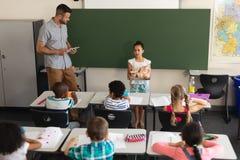 Hoge hoekmening die van schoolmeisje anatomisch model in klaslokaal verklaren royalty-vrije stock afbeelding