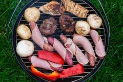 Hoge hoekmening, succulente lapjes vlees, burgers, worsten en groenten die op een barbecue over de hete steenkolen op een groen g Stock Afbeeldingen
