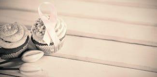 Hoge hoekmening van de Voorlichtings roze linten van Borstkanker op cupcakes met tulpen Stock Afbeeldingen
