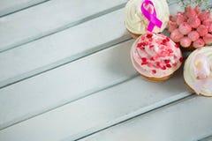 Hoge hoekmening van de Voorlichtings roze linten van Borstkanker op cupcakes Stock Fotografie