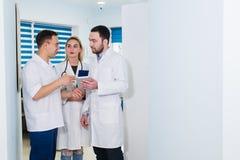 Hoge hoekmening van drie artsen in witte lagen die gesprek hebben bij het ziekenhuiszaal stock foto