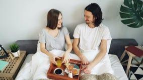 Hoge hoekmening van echtgenoot en vrouw die van ontbijt in bed het spreken het lachen genieten stock videobeelden