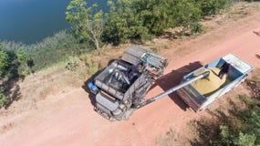 Hoge hoekmening van een rijstlandbouwer die een vrachtwagen laden Stock Foto's