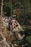 hoge hoekmening van gelukkige jonge proeffietsers die op rotsachtige klip ontspannen royalty-vrije stock foto's