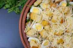 Hoge hoekmening van grote kleischotel met smakelijke caesar salade Stock Foto's