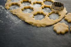 Hoge hoekmening van het gebakjesnijder van de bloemvorm op deeg Royalty-vrije Stock Foto's