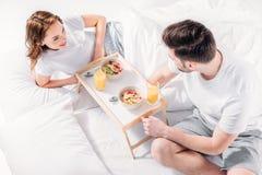 hoge hoekmening van jong paar die ontbijt in bed hebben stock fotografie