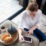 Hoge hoekmening van jonge vrouw die tablet gebruiken bij ontbijt Royalty-vrije Stock Fotografie