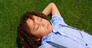 Hoge hoekmening van mengen-rasschoolmeisje het ontspannen op gras in schoolspeelplaats in zonneschijn 4k stock videobeelden