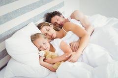 Hoge hoekmening van ouders die met dochter op bed slapen stock afbeeldingen