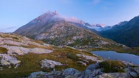 Hoge hoogte alpien meer in idyllisch land met majestueuze rotsachtige bergpieken Lange blootstelling bij schemer Brede hoekmening royalty-vrije stock afbeelding
