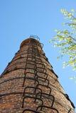Hoge industriële schoorsteenmening van onderaan Tegen de achtergrond van de hemel stock afbeeldingen