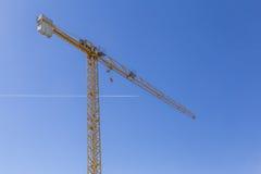 Hoge kraan op duidelijke blauwe hemel met een voorbijgaand vliegtuig Royalty-vrije Stock Fotografie