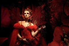 Hoge mannequin in rode kleding en fantasie s Stock Afbeeldingen