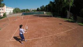 Hoge mening van vrouw het dienen op tennisgebied stock video
