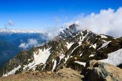 Hoge rotsachtige bergpiek met sneeuw en wolken in de Kaukasus royalty-vrije stock foto's