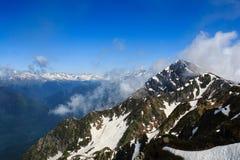 Hoge rotsachtige bergpiek met sneeuw en wolken in de Kaukasus royalty-vrije stock afbeeldingen