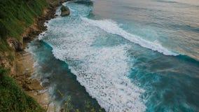 Hoge rotsachtige breuk vóór de oceaan Mening van een grote hoogte, op de golven die op de steenachtige kust rolden ongelooflijk stock video