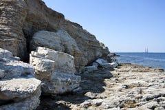 Hoge rotsen aan wal stock afbeeldingen