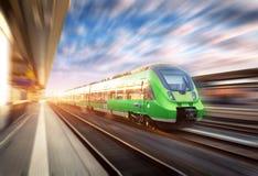 Hoge snelheidstrein in motie bij het station bij zonsondergang royalty-vrije stock fotografie