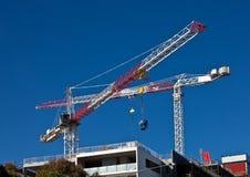Hoge stijgingskranen op bouwwerf Stock Afbeelding