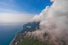 Hoge vlucht tegen de muur van wolken over de blauwe overzeese mening van een glijscherm proef, de zomervakantie in de Kaukasus in stock fotografie
