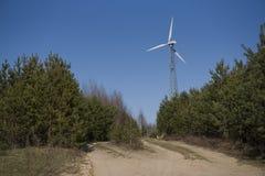 Hoge windmolen op de rand van het bos stock afbeelding