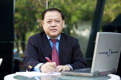 Hoger Aziatisch zakenman het schrijven voorstel stock afbeelding