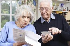 Hoger die Paar thuis met Rekeningen over Huisfinanciën ongerust worden gemaakt stock afbeeldingen