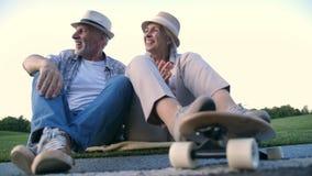 Hoger echtpaar die na het met een skateboard rijden lachen stock videobeelden