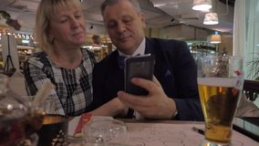 Hoger familiepaar die selfie in restaurant nemen stock footage
