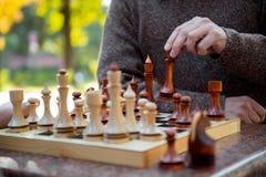 Hoger mannelijk wapen bewegend beeldje op schaakbord stock foto's