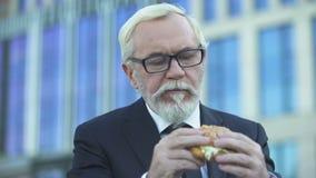 Hoger mannetje die in kostuum hamburger eten tijdens lunchtijd, die zich dichtbij bureaucentrum bevinden stock video