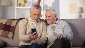 Hoger mannetje die nieuwe smartphone bejaarde vriend tonen, die moderne technologie gebruiken stock videobeelden