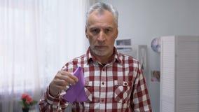 Hoger mannetje die purper lint tonen aan camera, de ziektevoorlichting van Alzheimer, zorg stock footage