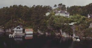 Hoger menings wit huis op rotsachtige kust met boten bij pijlers stock videobeelden