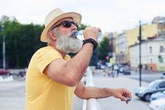 Hoger mensen drinkwater van een plastic fles met stedelijk ci Stock Foto's