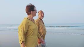Hoger op het strand lopen en paar die, steadicam schot spreken stock videobeelden