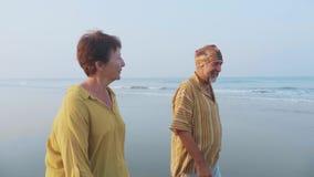 Hoger op het strand lopen en paar die, steadicam schot spreken stock footage
