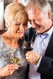 Hoger paar bij bar met glas wijn ter beschikking Royalty-vrije Stock Afbeeldingen