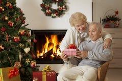 Hoger Paar dat de Giften van Kerstmis ruilt Stock Foto's