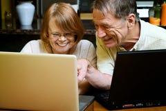 Hoger paar dat laptop computers thuis met behulp van Royalty-vrije Stock Fotografie