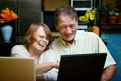 Hoger paar dat laptop computers thuis met behulp van Royalty-vrije Stock Afbeelding
