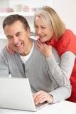 Hoger Paar dat Laptop thuis met behulp van stock afbeelding