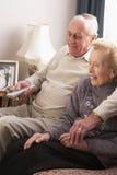 Hoger Paar dat op TV thuis let Royalty-vrije Stock Foto's